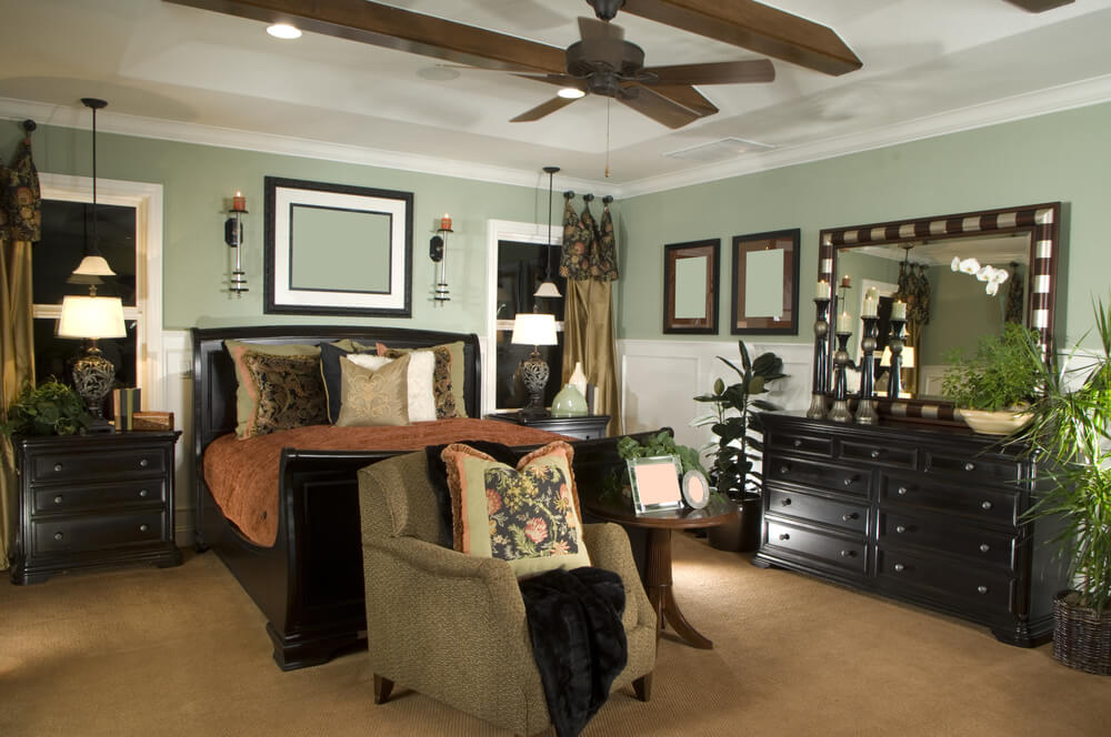 Beautiful bedroom sets luxury modern and italian collection with a master black bed and black themed furniture. The walls are pale green and the ceiling has a dark fan. The piece of resistance is monochromatic wall panting that matches the color of the wall.