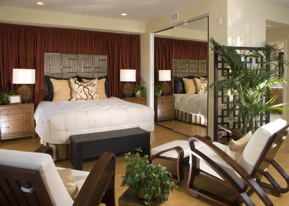 Modern master bedroom furniture arrangement ideas with double mirror doors, behind there are shelves for additional storage. Two really comfortable modern looking wood chairs with a small table in the middle and a plant on it. Tree large beige and black pillows on the luxurious bed.