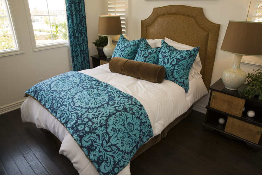 Photos of luxury bedrooms decorated in blue - blue drapes and blue pillows with blue bed cover. Dark hardwood flooring with brown pillow, brown bed frame and small white windows.