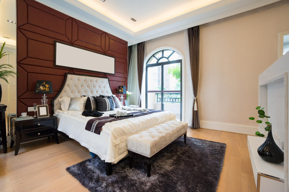Romantic master bedroom decorating ideas pictures with a small white bench at the foot of the white bed. Dark red wall color in contrast with white and picture at top of the bedding.
