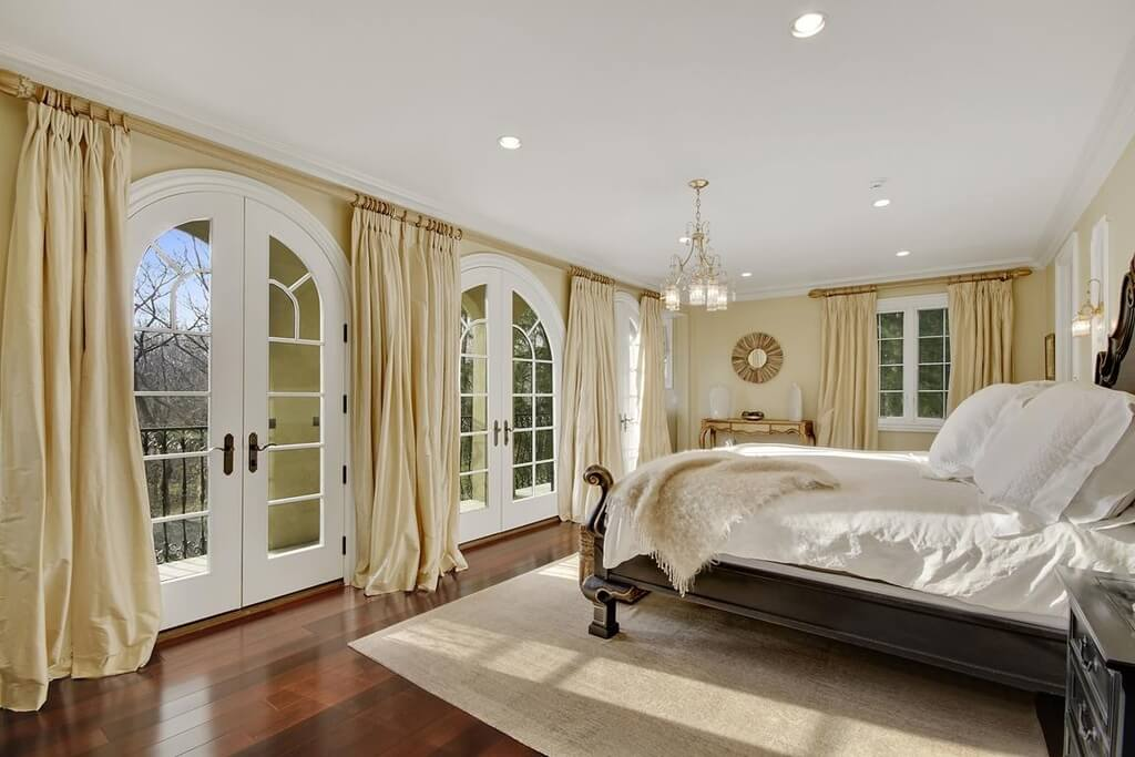 Traditional master bedroom decorating ideas pictures - with a beautiful balcony view to the nature. Big white double doors, white & beige long drapes and carpet, are in contrast with the shiny dark brown hardwood floor.