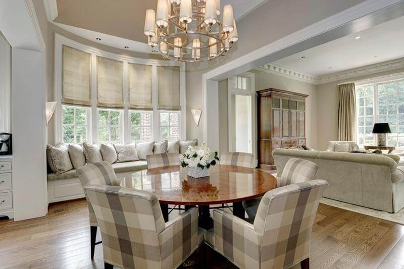 Circular Dining Room Design with a shiny polished honey wooden dining table that can accommodate five comfortable squared patterned chairs. Also above there is a white chandelier.