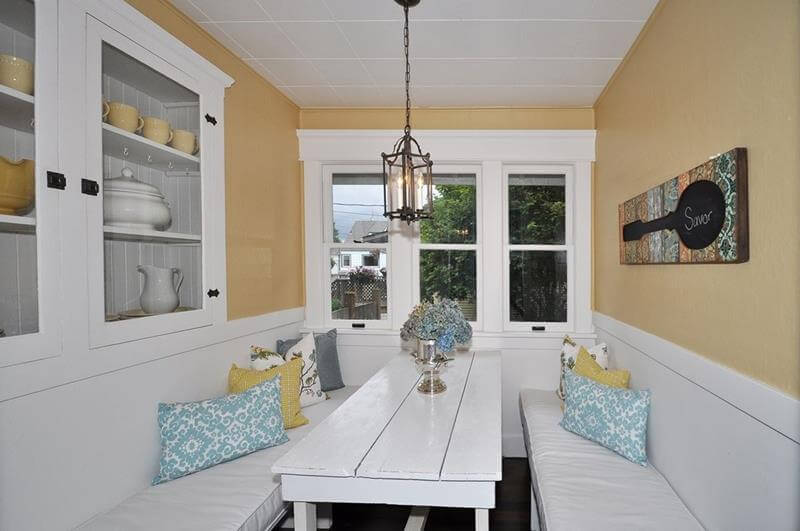 Cottage Dining Room with a small white wooden dining table and on each side a white bench with multi color pillows. Also the walls are yellow painted with small ornaments.