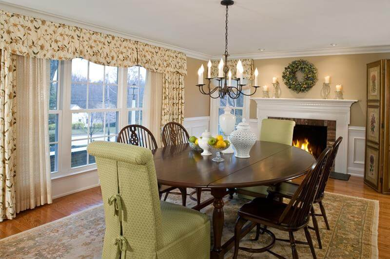 Country Dining Room Design with a white stone fireplace and walls that are painted beige and yellow. Also an oval hardwood dining table with dark chairs as decor.