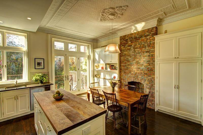 Dining Room With Brick Fireplace made out of orange and beige bricks, small honey wood dining table with cozy chars with a rustic design and pattern on the ceiling.