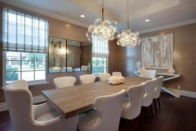 Dining Room With Chandeliers design - a beautiful dining room decor with nine white chairs and light brown walls with mirror and paintings, Also two beautiful chandeliers.