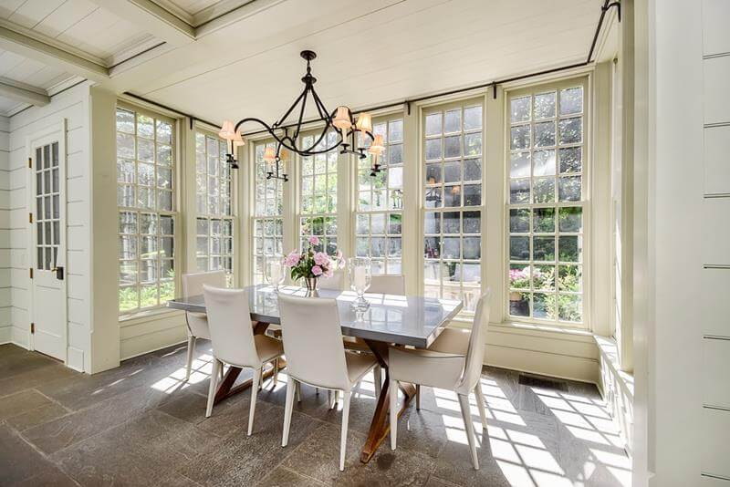 Dining Room with Classic Styling with a rustic design, a country decoration design. Large windows that lets the sunlight pass in. Also the floor is made out of large granite tiles.