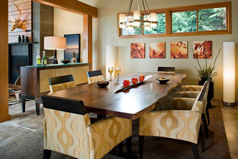 Dining Room with Concrete Floors with yellow and beige color mix. The bend offers plenty of visual effect in contrast with the dark wood dining table.