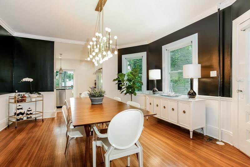 Dining Room with Mid-Century Styling with beautiful satin black walls and honey wood hardwood flooring. In the center of the room there is a large table with white chairs.