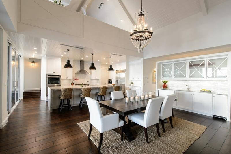 Dining Room with Wet Bar with a very high A shaped ceiling, with white beams that offers more resistance to the structure. In contrast with the dark hardwood flooring and beige rug.