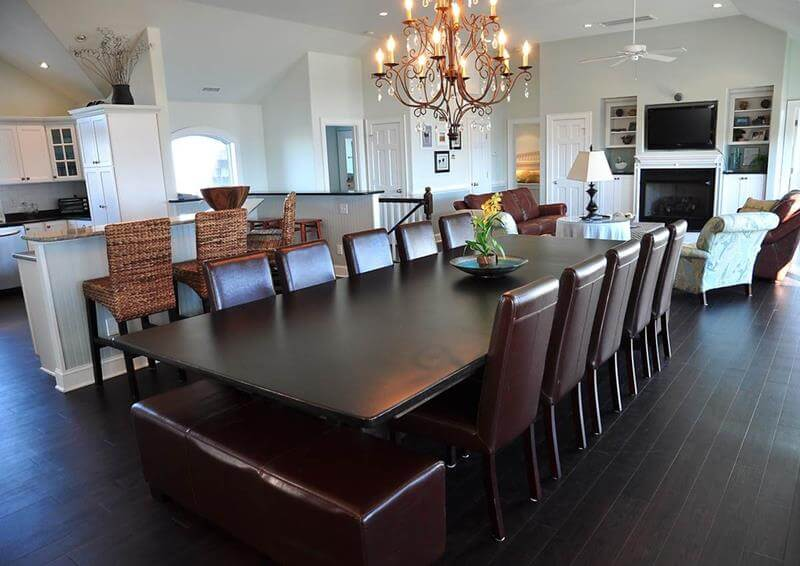 Dining Room with Wood and Leather concept - A very large dark wood dining room table with 10 leather chairs and a dark leather bench. In contrast with the white walls and golden chandelier.