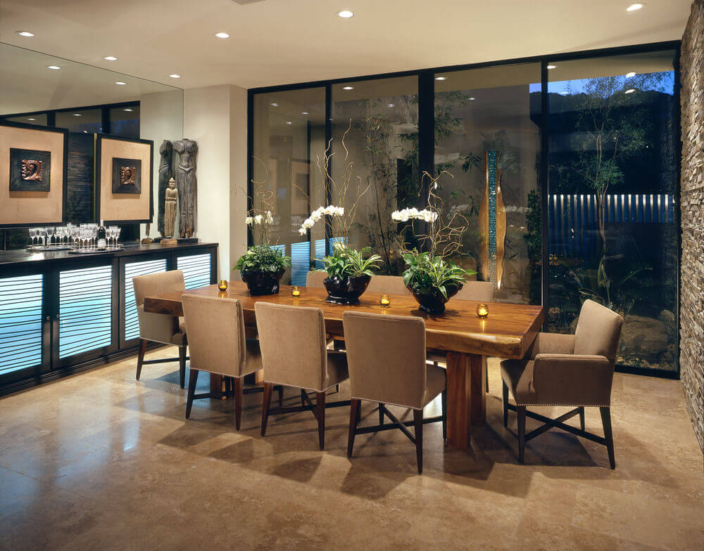 Beautiful dining room ideas and design with wooden table, polished marble floor and brick wall. Lightening is provided by the ceiling spots that can be adjusted manually. Also large windows that replace an entire wall, perfect in day time to let natural light enter the dining room.