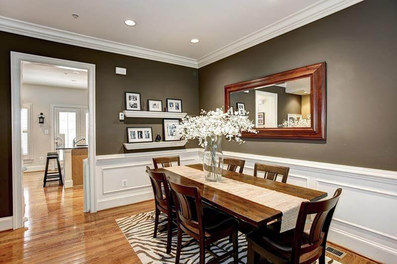 Grey and White Dining Room with a zebra design rug and white ceiling with spotlights. Also a shinny and polished honey wood hardwood flooring design. And a large mirror with a large wooden frame.