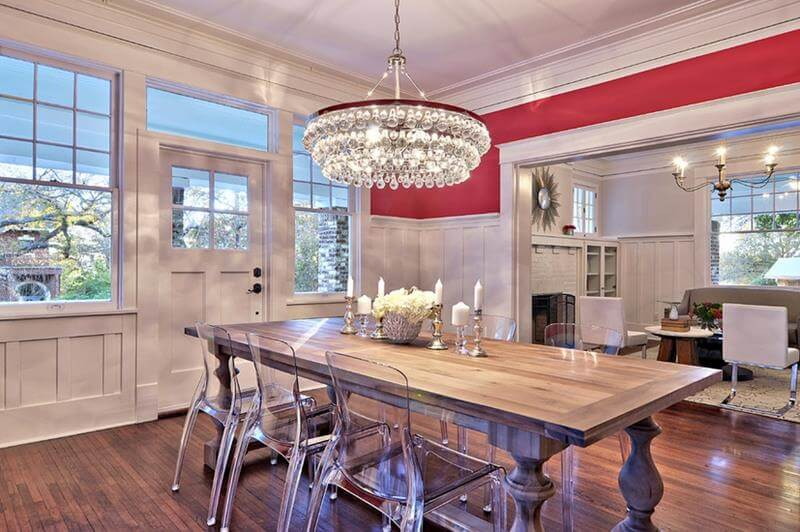 Red and White Dining Room with red wall painting and white walls and windows frames as also white entrance door. A grey hardwood dining room table is present with glass chairs.