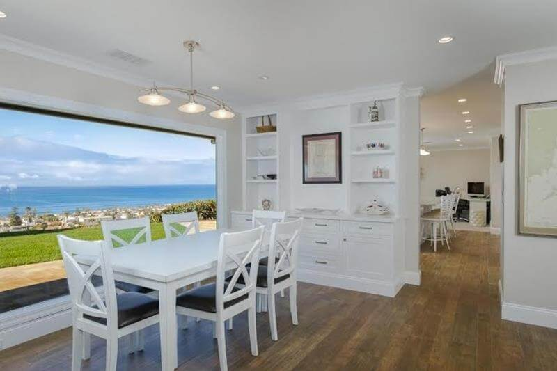 White Dining Room Design with splendid view overlooking the Ocean. Also white dining room furniture with white chairs and a white dining table in contrast with a satin polished hardwood floor.