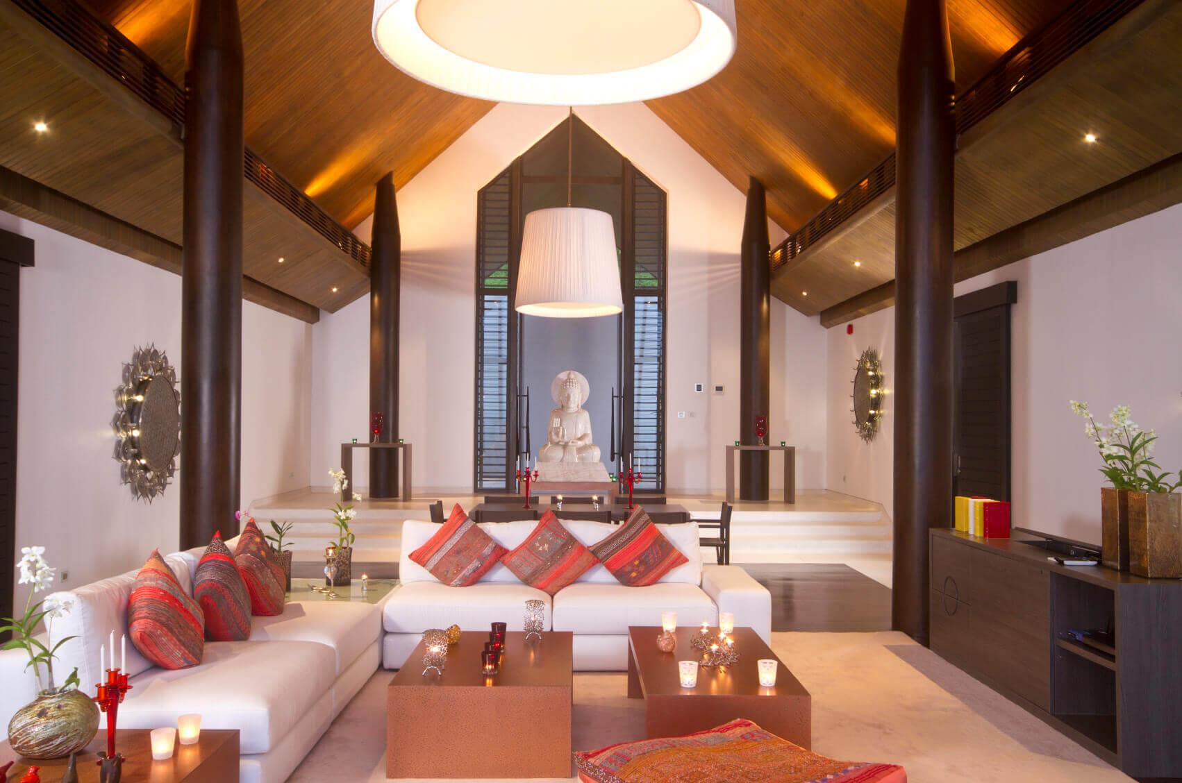 Asian living rooms with for construction pillars, sloped ceiling, white L shaped sofa with multiple red pillows. In the center there is a Buddha statue. Small light spots that light up the ceiling.