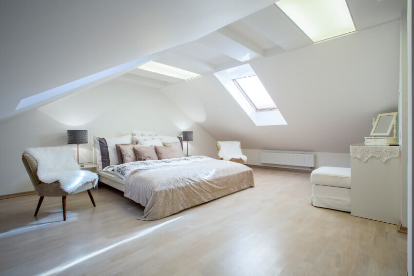 Attic master bedroom ideas - A truly unique design with a large ceiling, large windows in the ceiling and a king size bed with two dark colored night lamps, and white furniture.