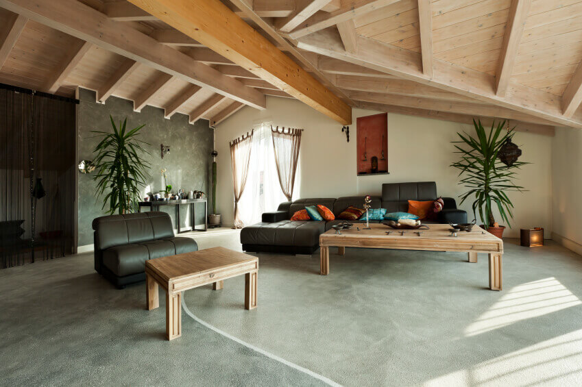 Attic living room ideas with dark furniture with a large light beige wooden coffee table and a small table. Also sloped ceiling with plants added for contrast and that blend with green wallpaper wall.