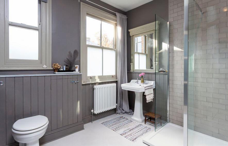 Bathroom cool gray - A small and cozy bathroom with rustic elements and gray wallpaper design. Also the shower is made out of glass and has a beige brick wall.