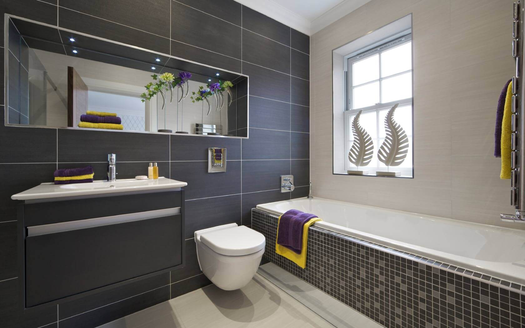 Modern looking bathrooms black tile with a wall made out of big rectangular black tiles and the bathtub has small squared black tiles in conrtast with the other wall that has small rectangular beige tiles.