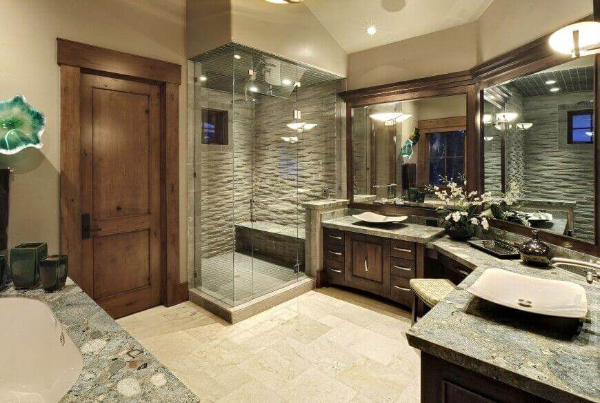 Bathrooms corner showers with large mirrors and dark wood cabinets and shelves. A large bricked shower with natural tone an d large tripe sink bathroom area.