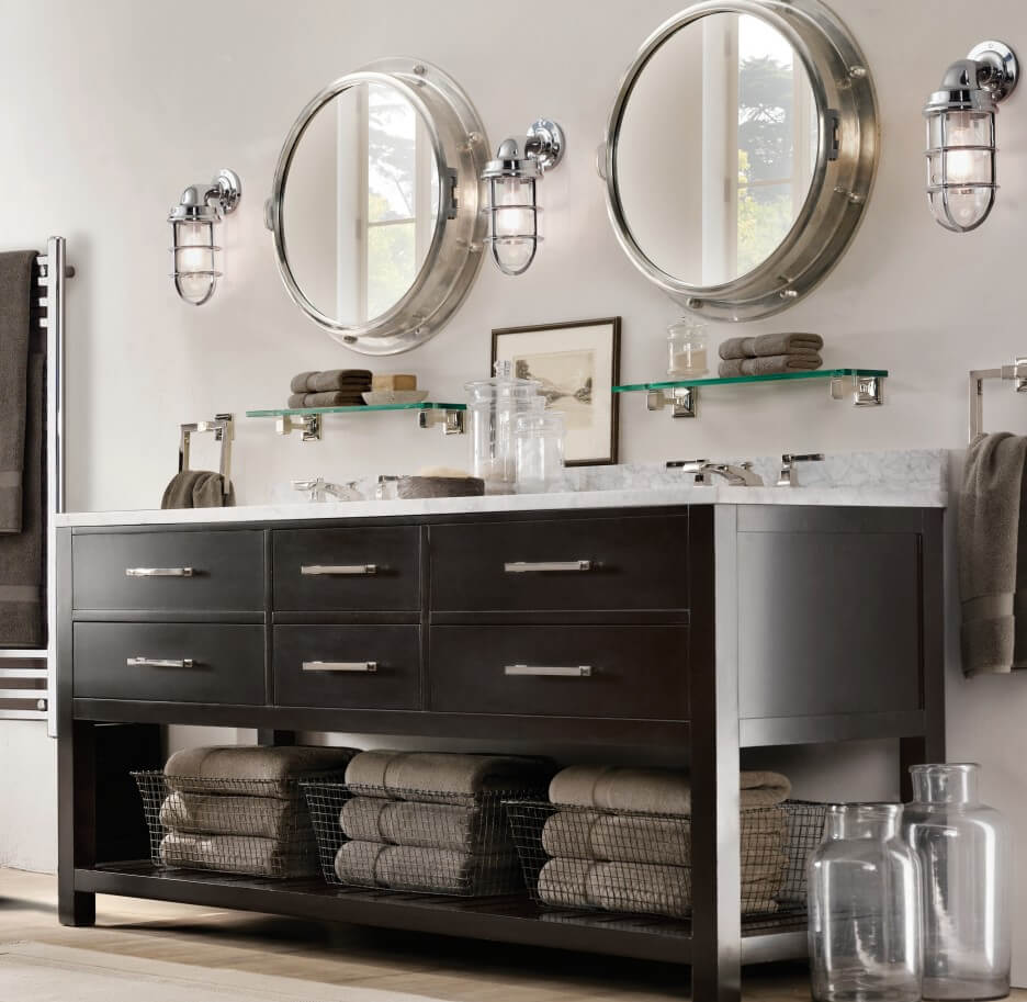 Bathrooms round mirrors with metallic round frame, two tone sinks with white stone top and large storage are underneath made out of black wooden cabinets with compact drawers.