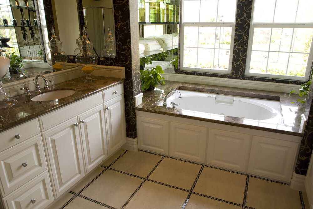 Bathrooms white cabinets with white furniture sets, white cabinets with white drawers, white squared tiles flooring that complements the hard granite top of the bathtub and sink.