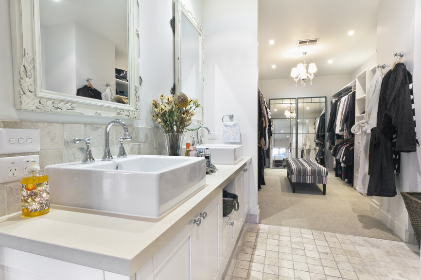 Beautiful white bathrooms with walk in closets - with a multi patterned ottoman / bench where you can find an open wardrobe with all your favorite cloths.