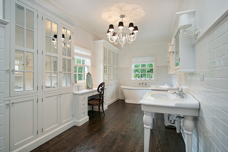 Unique contrast between the bathrooms with dark floors and the white furniture that accompanies the room. The only dark elements besides the flooring are the dark makeup chair and the chandelier insertions.