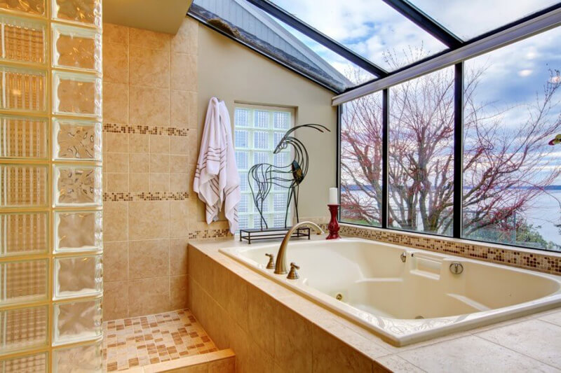 Superbly designed bathroom with skylights view, The half of the ceiling and the wall is made of glass with metallic frame. In addition the beige bathtub blends with the beige shower design.