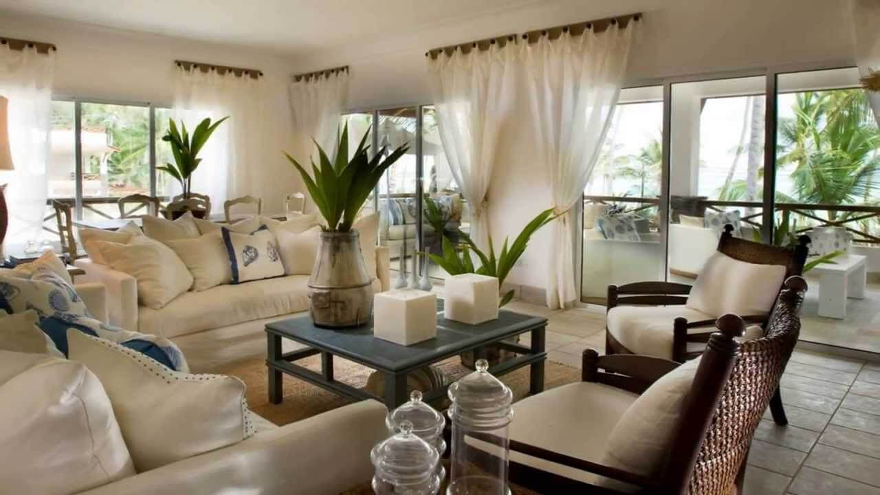 Beautiful living room designs with white furniture and blue coffee table. Tho white sofas and two chairs made of dark wood. Also made white drapes, large windows and doors made of glass.
