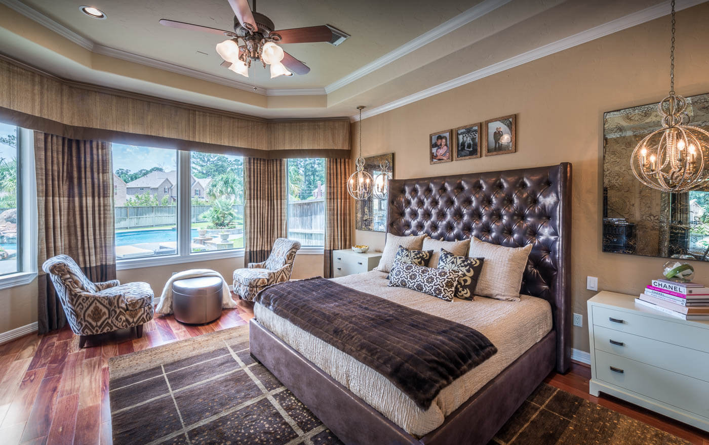 Bedroom designs top designers worldwide. In this photo you can see a king size bed with a big leather headboard with dark and flooring. Also there is a sitting area with two comfortable chairs and a small coffee table.