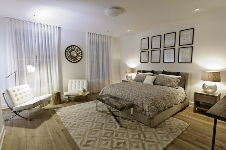 Simple designs about bedrooms area rugs with modern white and gray pattern designs. Small metallic loveseat and light gray hardwood flooring. Also a reading lamp near the white chairs form the sitting area.
