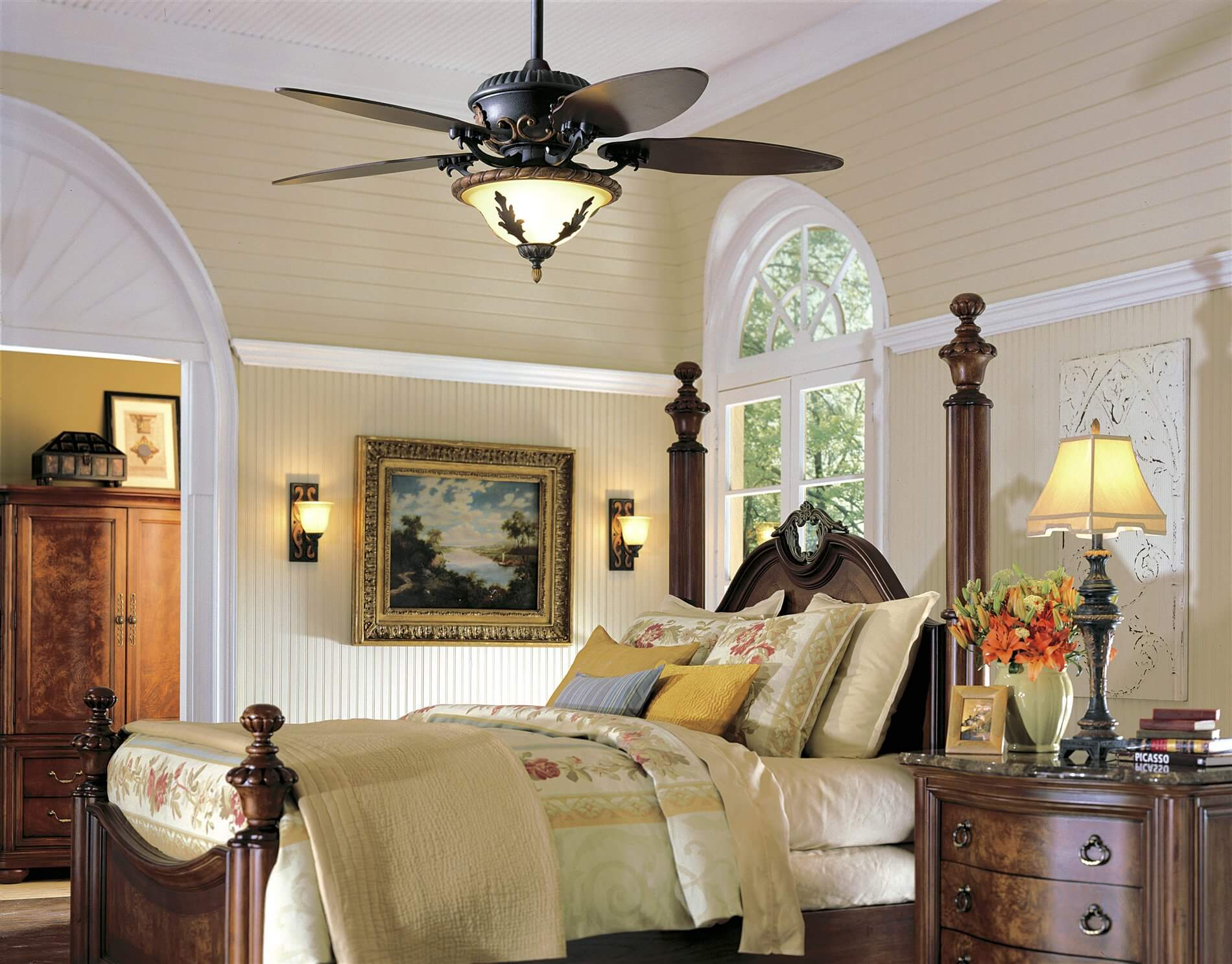 Beautiful designed bedroom with metallic ceiling fan, a large wooden wardrobe in the background, beige wall theme, and a hardwood bed frame and cabinet with night lamp on it.