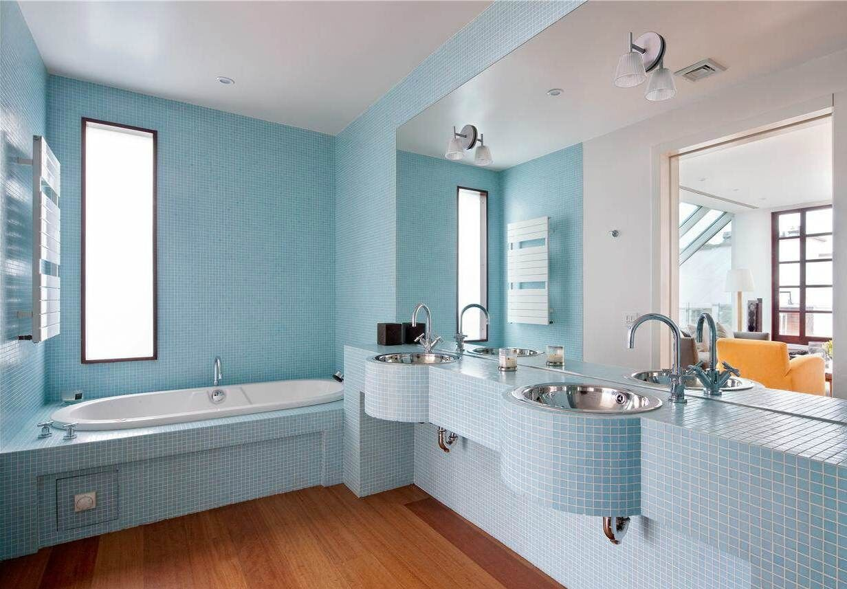 Blue master bathroom designs with small blue tiles that cover the walls, the sinks and the bathtub. In contrast with the brown mat finished hardwood flooring.