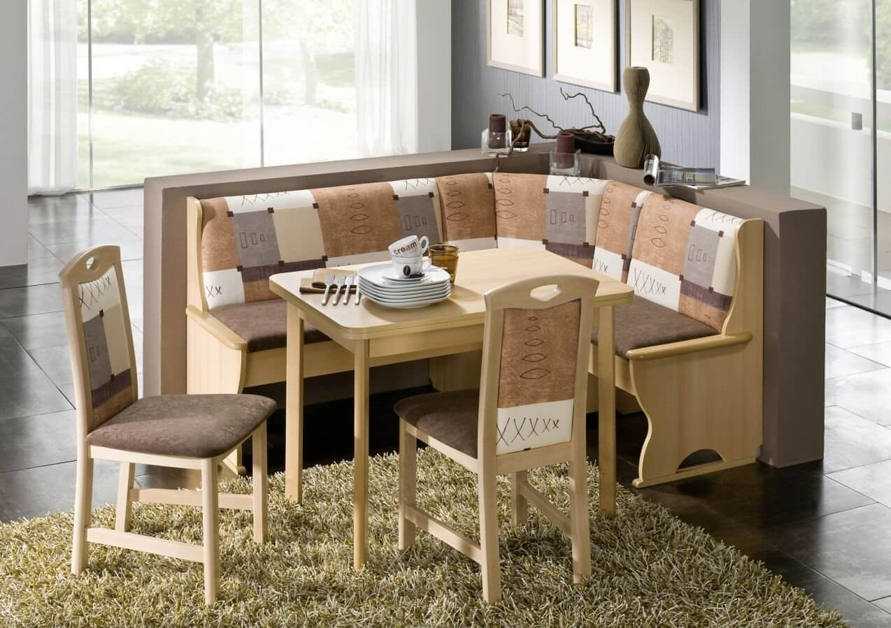 Small corner dining sets made of beige wood with multi color fabric in contrast with floor that is made of dark grey tiles. Also with large windows that let the natural light enter the room.