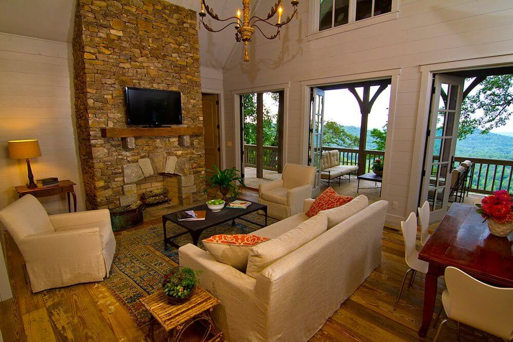 Cottage living rooms with beautiful stone fireplace with natural wooden floor beige furniture and big three double doors with glasses overlooking the large balcony with tow deck sofas.