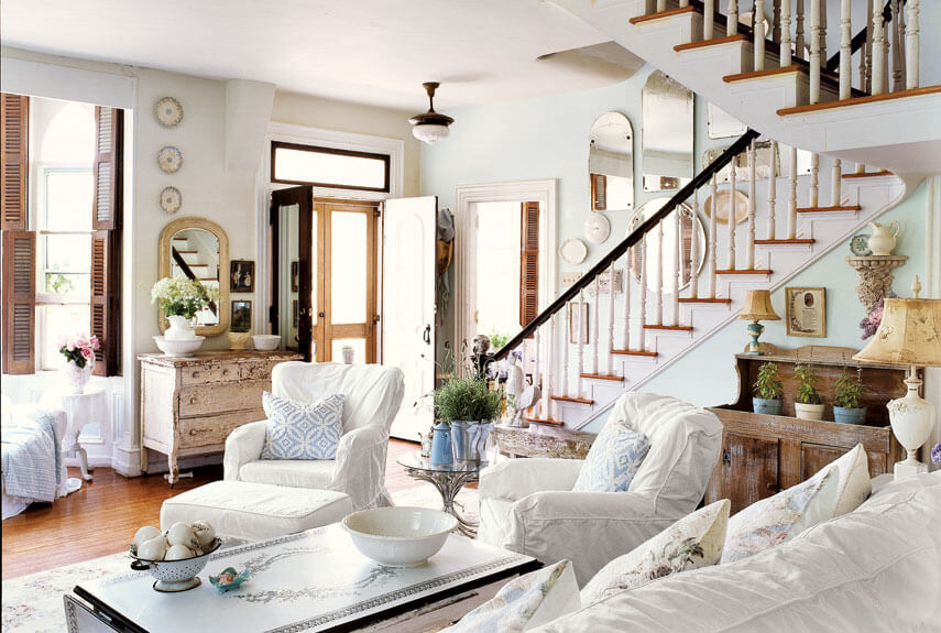 Rustic and cozy living room designs with many wall mirrors and white furniture. White coffee table and white fabric covers the chairs and sofa.