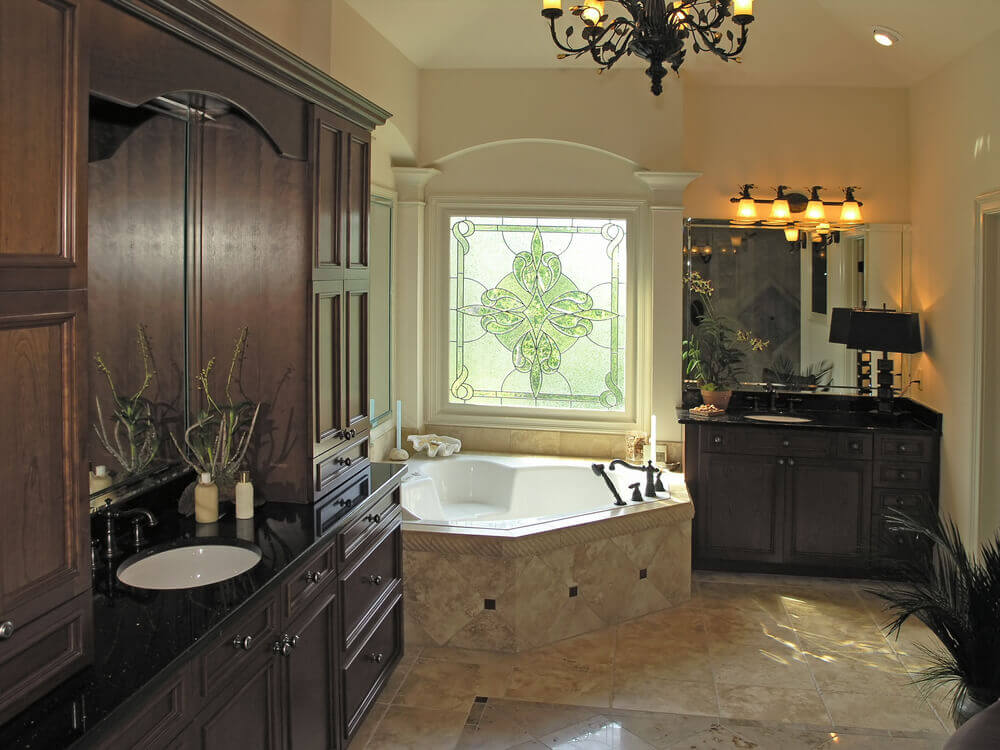 Custom bathrooms that allows customization. Two black granite sinks with dark hardwood cabinets with big drawers, also in contrast with white large bathtub and a Murano styled glass window.