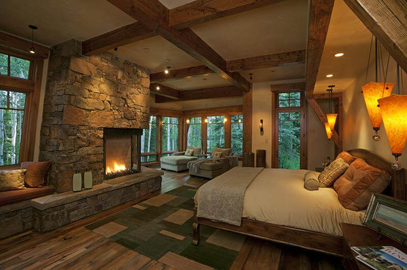 This is a custom master bedroom designs inspired from a mountain cottage with a brick fireplace in front of the master bedroom. The ceiling has wooden beans that traverse the room.