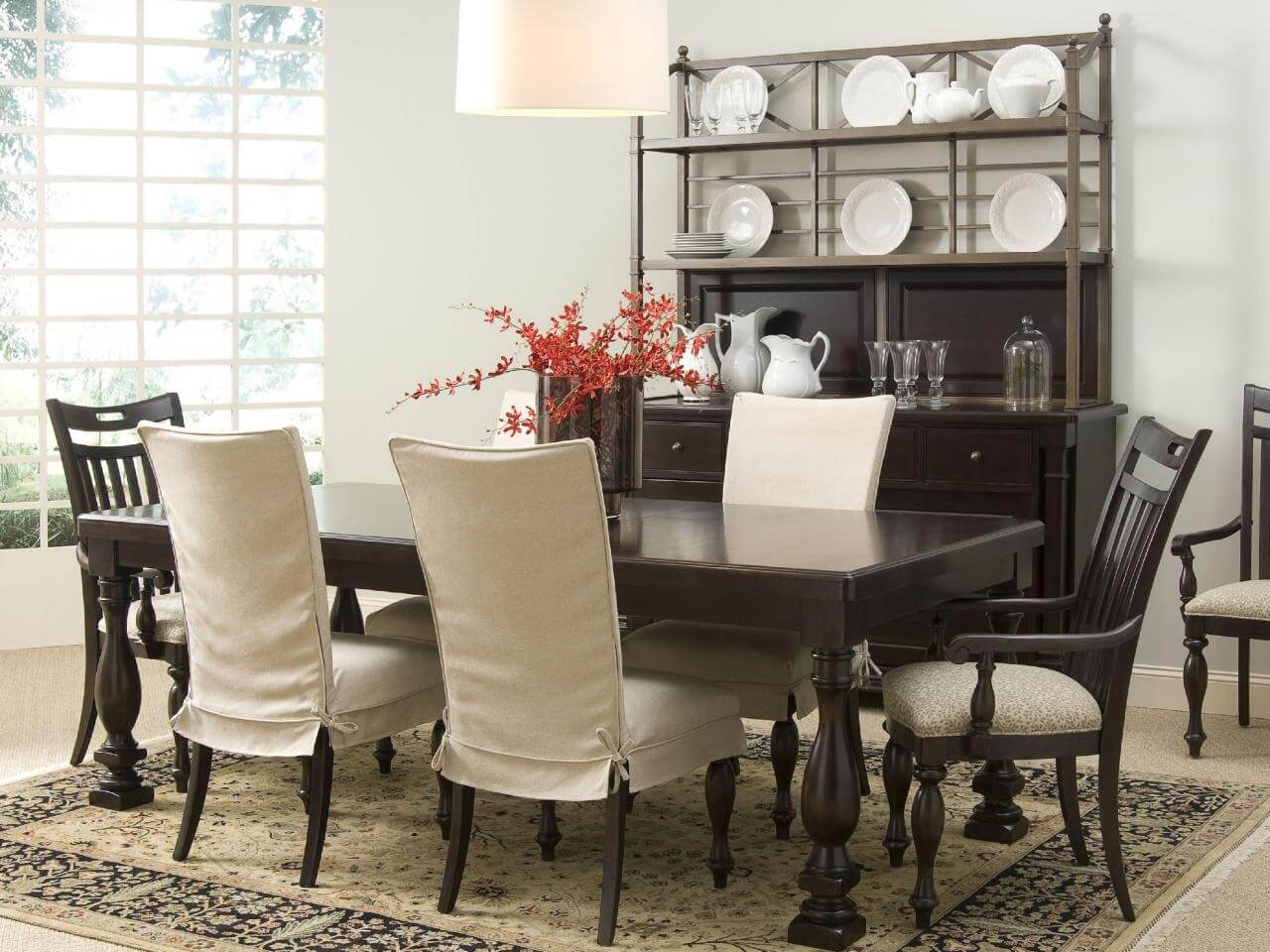 These great dining rooms have upholstered chairs for extra elegance with a multi floral carpet and back wood chairs and table. In contrast with beige fabric that overs the chairs.