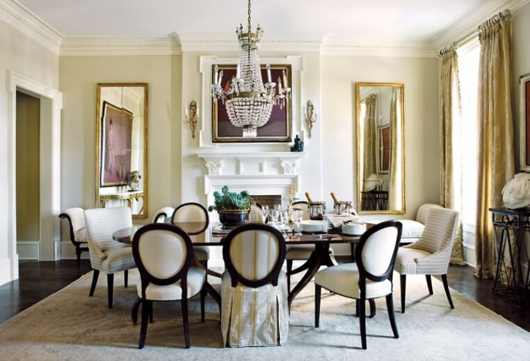 Elegant dining room designs with a white fireplace and large windows with golden drapes and two large mirrors golden frames. This is in contrast with the dark wood floor and chair frames.