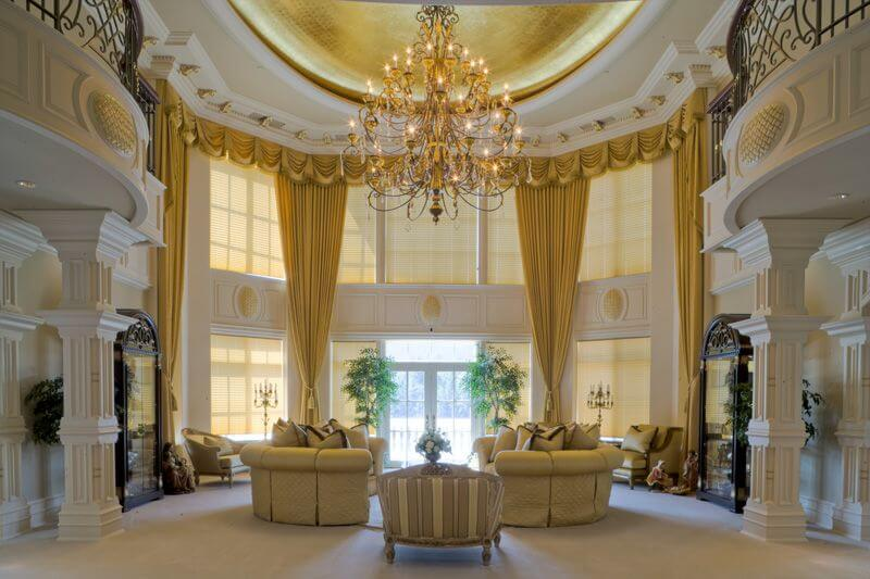 Incredible living rooms with tall ceiling, large and beautiful chandelier, two white construction pillars with classic ornaments, two golden sofas and tall golden drapes.