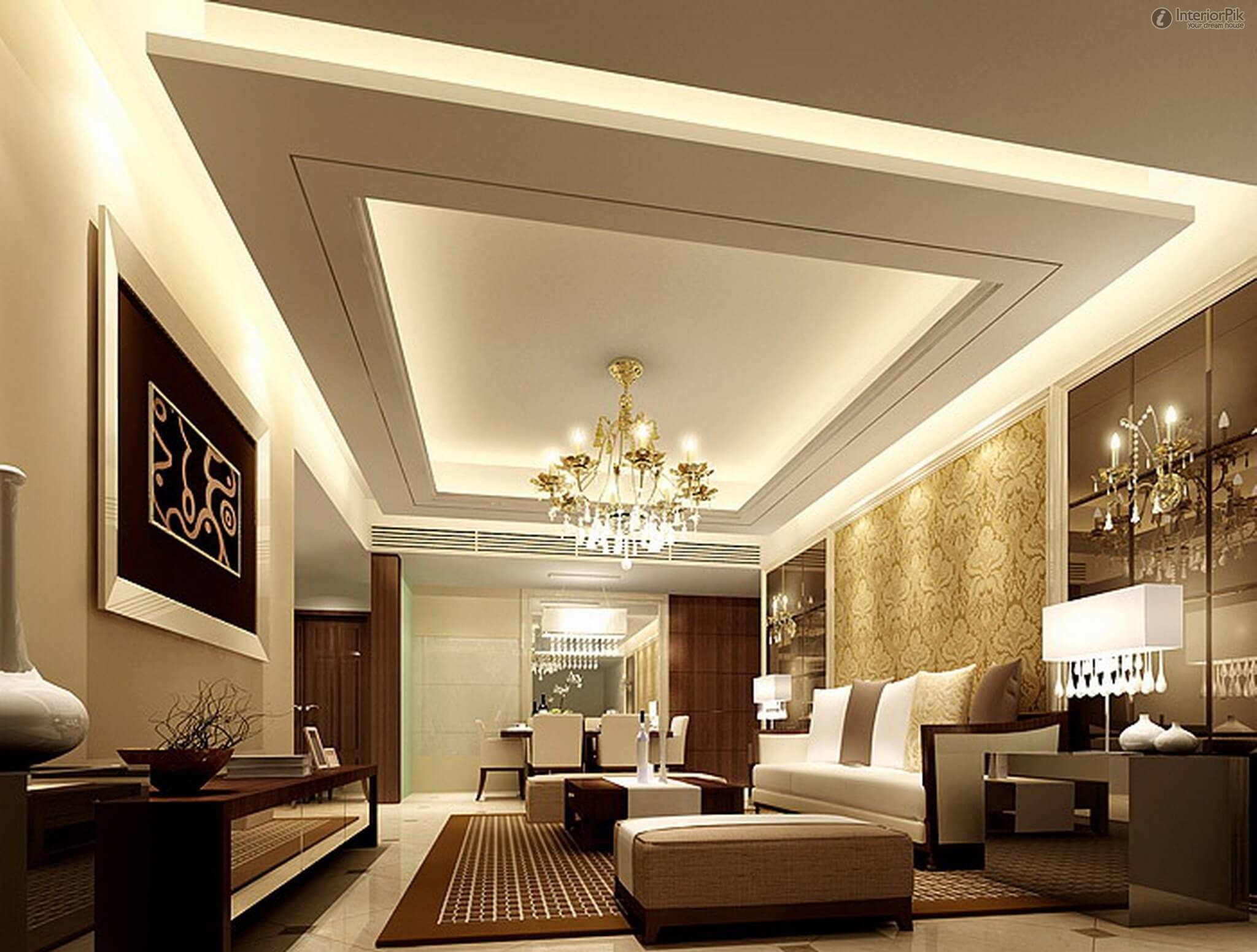 Living room ceiling ideas with many light spots that are hidden and only illuminates the ceiling and the walls. in the center of the ceiling there is a chandelier and also a golden wallpaper on the wall.