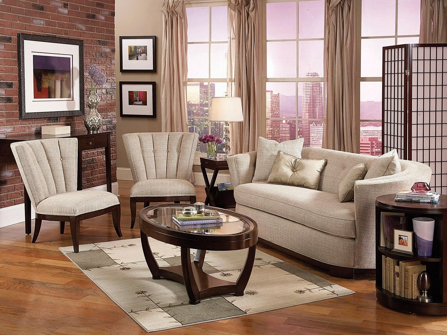 Comfortable living room chairs that fit great accompanied by a two set sofa, one oval dark wood small tea table with glass top, red brick wall and large light drapes.