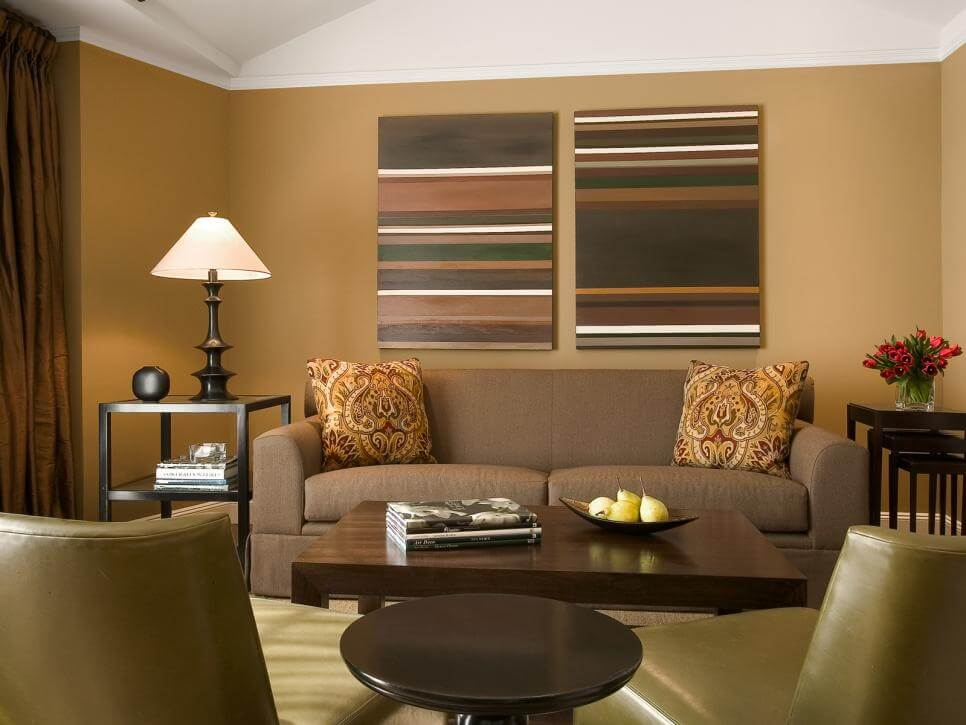 Earth tone living room colors. As you can see there are a couple of predominant colors like earth brown furniture and coffee table, dark green chairs and tow earth tone stripes painting hanging on the wall.
