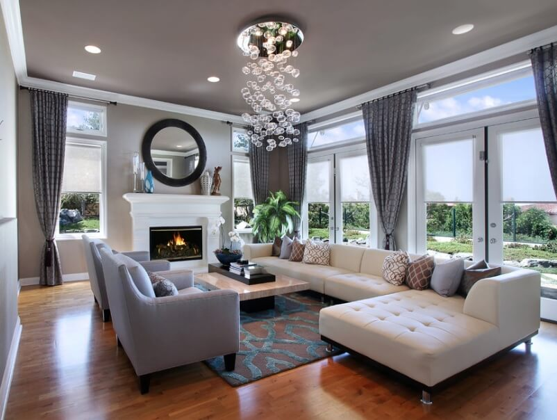 Living room decor ideas for an extraordinary house. Large double doors that let the natural light inside, a modern chandelier and light spots in the ceiling and a big rounded mirror on top of the white fireplace.