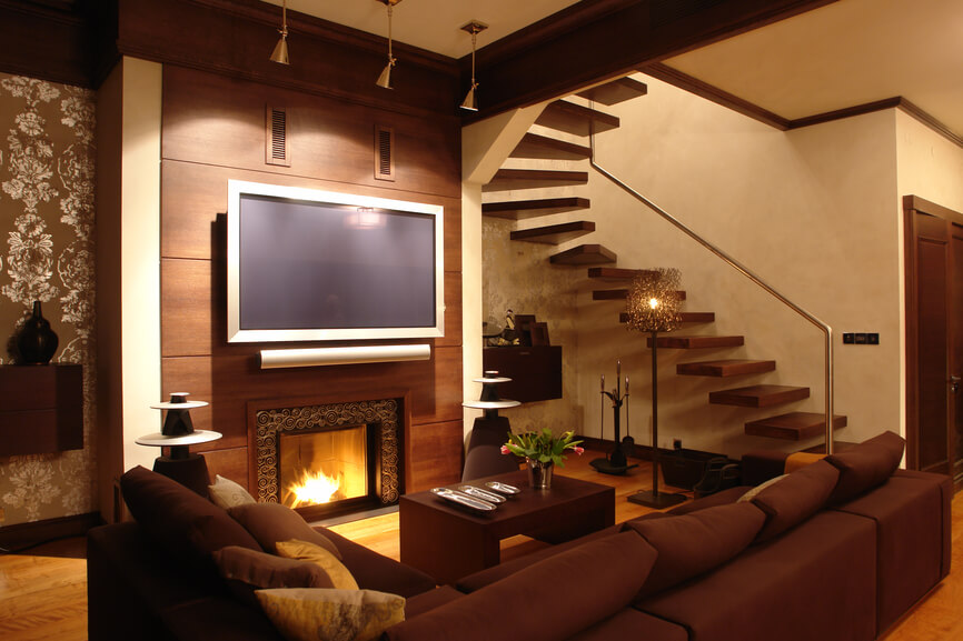 Living room designs with beautiful woodwork wall and with interior staircase, A huge TV on top of the small fireplace. Beige wallpaper walls and dark color l shaped sofa.