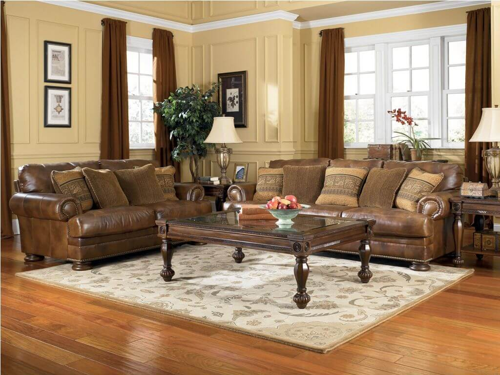Elegant leather living room sofas with brown pillows and brown drapes and flooring. In contrast with floral pattern rug and light color walls.