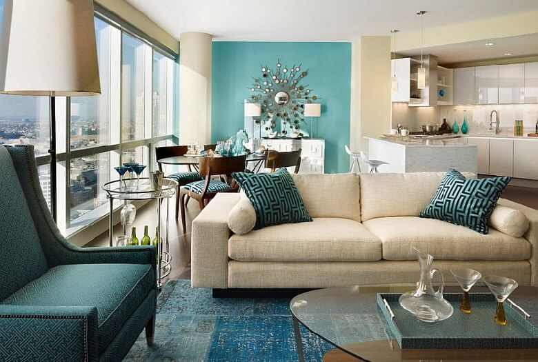 Luxurious living room themes with light blue rug on the floor, blue patterned chair design and a turquoise wall and two pillows. Also a kitchen area with white furniture.